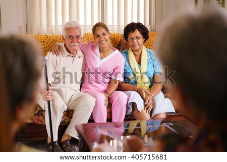Old people in geriatric hospice: Elderly man and woman hugging a young nurse, showing a friendly relationship between personnel and patients. - stock photo