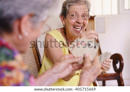 Old people in geriatric hospice: group of senior women playing cards and having fun together. An aged lady wins the game and shows a card to her rival - stock photo