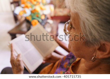 Old people in geriatric hospice: senior woman with eyeglasses and miopia problems sitting on chair and reading a book.  - stock photo