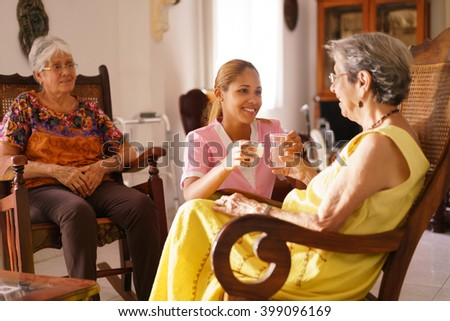 Old people in geriatric hospice: young attractive hispanic woman working as nurse helps a senior woman. She gives a water glass and prescription medicine to the aged patient - stock photo