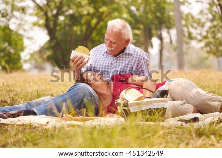Old people, senior couple, elderly man and woman in park. Retired seniors eating food at picnic - stock photo