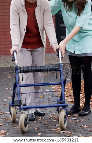 Old person learning to walking with walker - stock photo