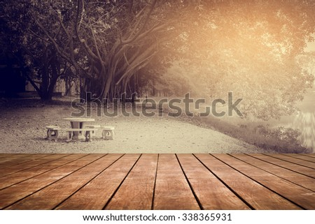 old perspective wooden floor with blur image of table set and banyan tree - stock photo