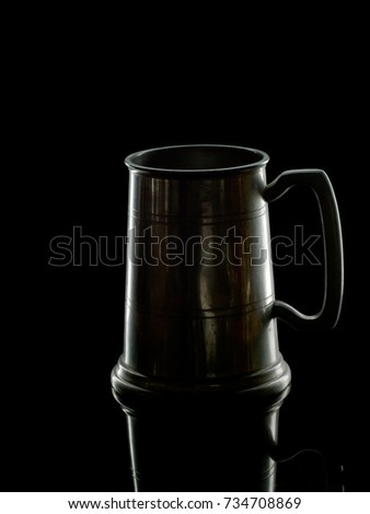 Old pewter tankard for beer or cider back lit. Dark dramatic image. Black background.
