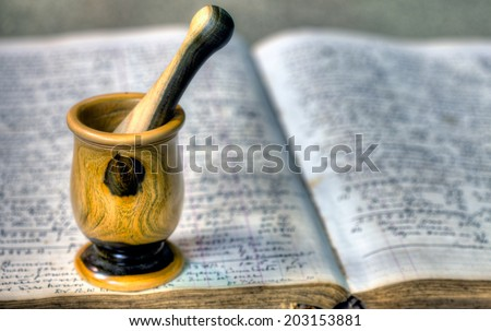 Old pharmacy book with mortar and pestle - stock photo