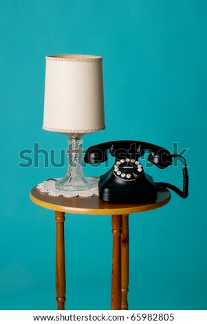 old phone and lamp on table - stock photo