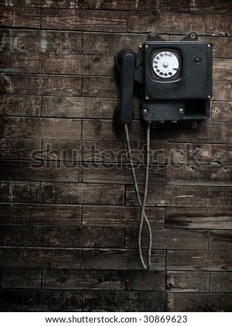 Old phone on a wooden wall. monochrome - stock photo