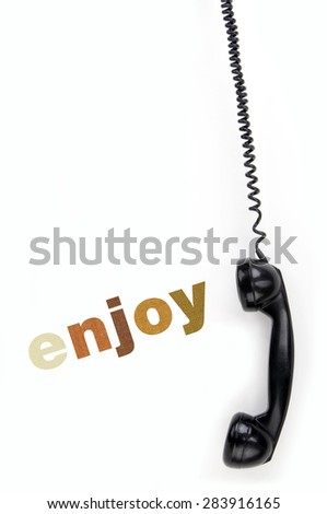 Old phone receiver with inscription enjoy - stock photo