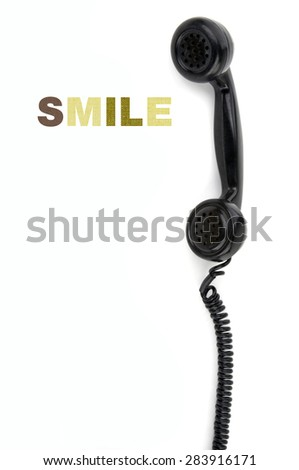 Old phone receiver with inscription smile - stock photo