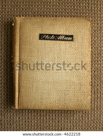 Old photo album on the floor carpet - stock photo