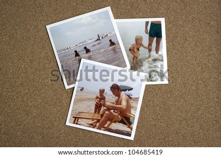 Old photo album photographs from the early 1970's of family at a beach on a bulletin board.