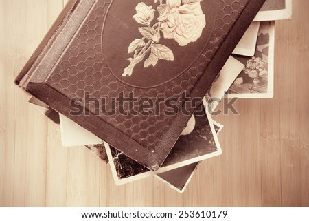 Old photo-album with retro pictures inside it on wooden background. - stock photo