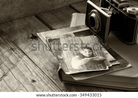 old photo camera, antique photos and old book on wooden table. black and white style photo. selective focus - stock photo