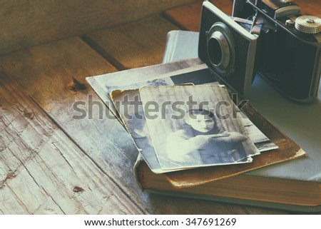 old photo camera, antique photos and old book on wooden table. retro filtered image - stock photo