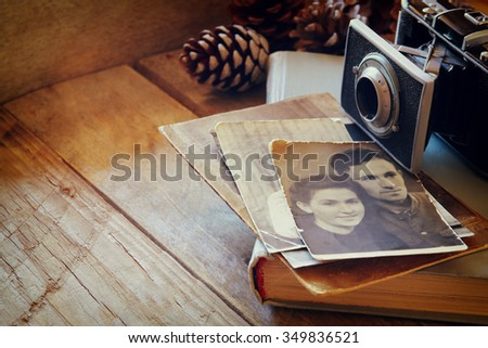 old photo camera, antique photos and old book on wooden table. selective focus  - stock photo