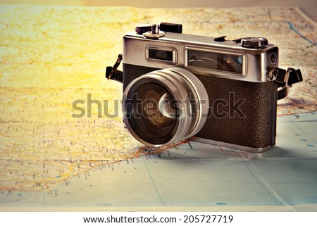Old photo camera on old map - stock photo