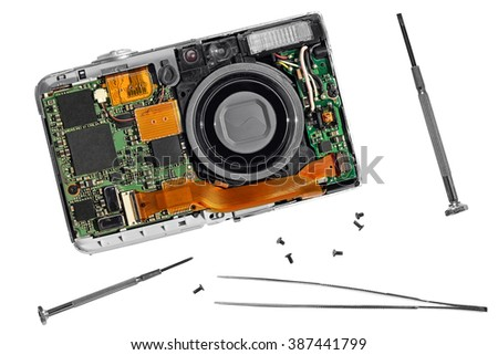 Old photo camera repair with screw drivers and pincers (forceps) isolated on a white background