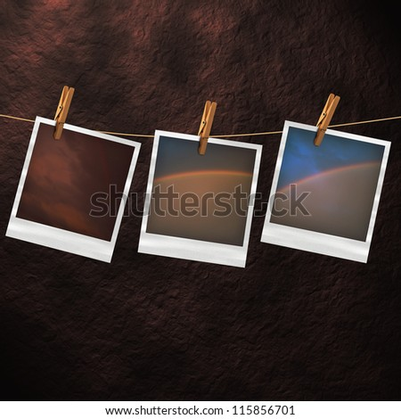 Old photo cards hanging on a clothesline against a stone background - stock photo