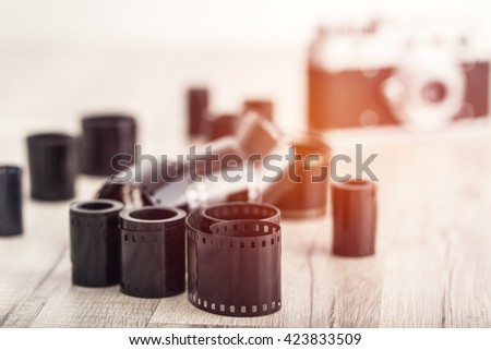 Old photo film rolls and old film camera on the background. - stock photo