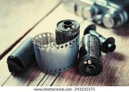 Old photo film rolls, cassette and retro camera on background. Vintage stylized. - stock photo