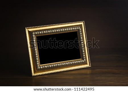 old photo frame on the wooden table - stock photo