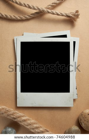 Old photo frames on antique paper with rope and marine stones - stock photo