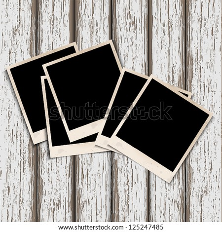 Old photo frames on old wooden background. Raster version - stock photo