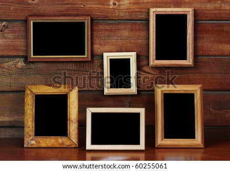 old photo frames on the wooden wall and table - stock photo