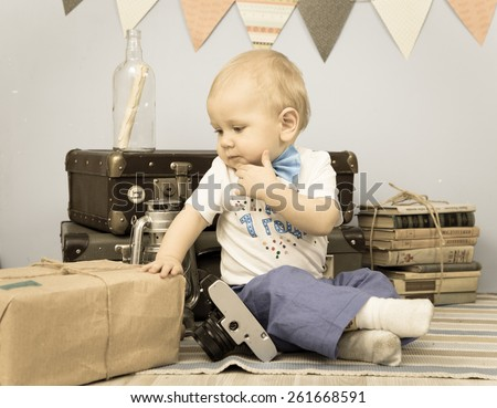 Old photo of sad baby looking at mail package indoors - stock photo