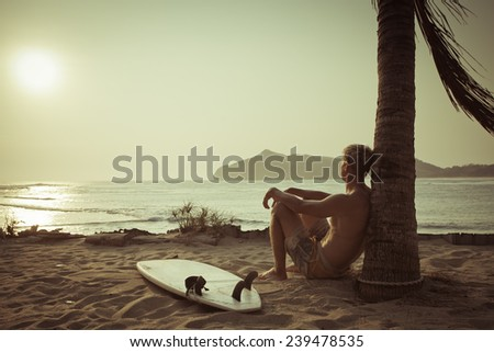 Old photo of surfer near the palm with surfboard on beach - stock photo