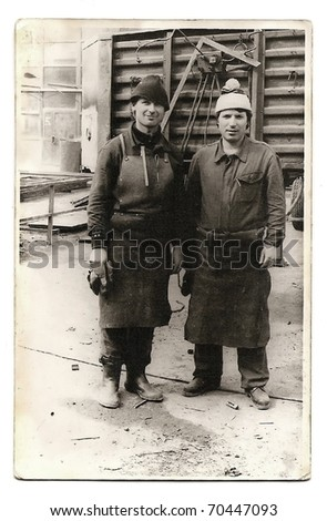 Old photo of two factory workers - stock photo