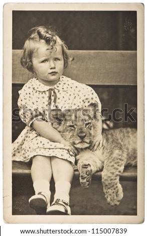 old photo portrait from little girl with tiger baby. vintage picture ca. 1930-40 - stock photo