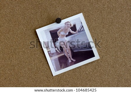 Old photograph from the 1960's of a woman and her car posted on a bulletin board. - stock photo