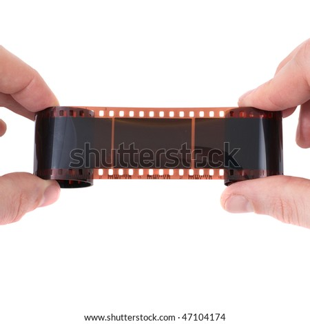 Old photographic film in the hands on white background - stock photo
