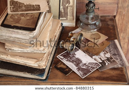Old photos, post cards, books, opera glasses and oil lamp on wooden background. - stock photo