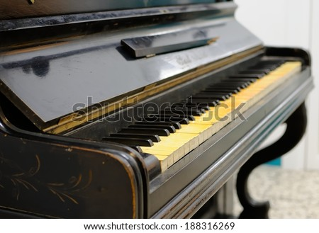Old piano with ivory keys that have become yellowed over time - useful image for cleaning/restoration themes - stock photo