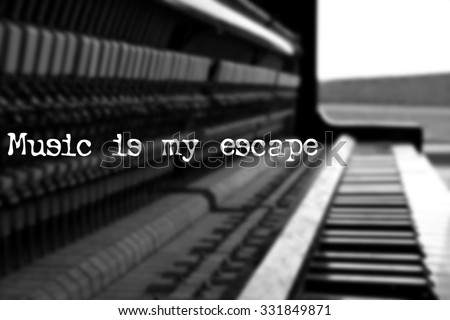 Old piano with quote - Music is my escape  - stock photo