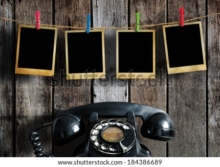 Old picture frame hanging on clothesline and old telephone on wood background. - stock photo