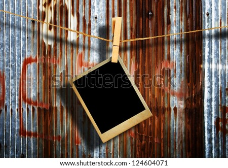 Old picture frame hanging on clothesline on grunge wall. - stock photo