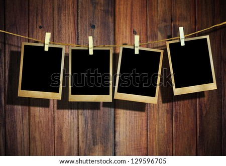 Old picture frame hanging on clothesline on wood background. - stock photo