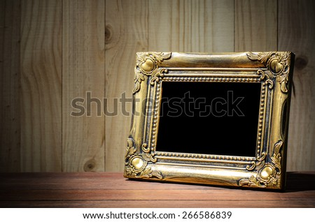 Old picture frame put on wood background. - stock photo