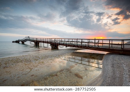 old pier at the sea during sunset - stock photo