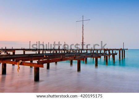 Old pier in the sea at dawn - stock photo