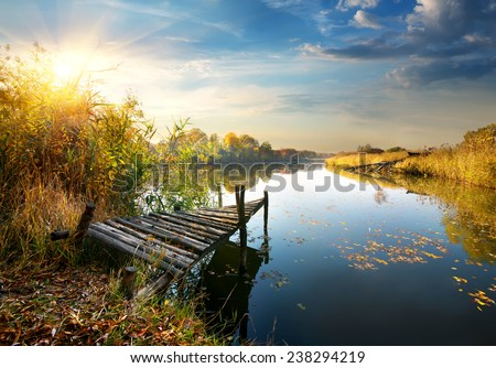 Old pier on autumn river at sunset - stock photo