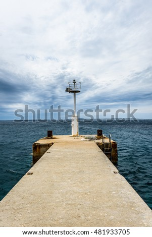 Old pier with a lighthouse beacon and calm sea. Rusty moorings on concrete pier on a windy day with dramatic clouds. Adriatic sea -  Silba, Croatia.