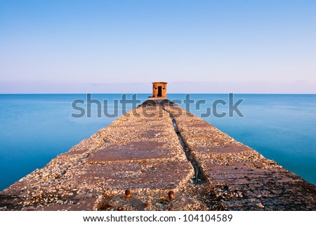 old pier with guard house extending into the sea. Long exposure - stock photo
