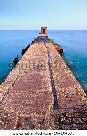 old pier with ruined guard house, long exposure - stock photo