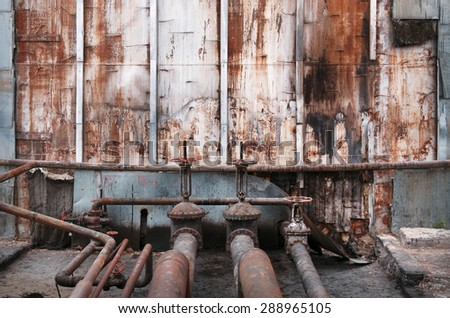 old pipes and valves at an abandoned oil terminal - stock photo