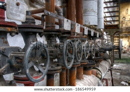 Old pipes with valves and label - stock photo