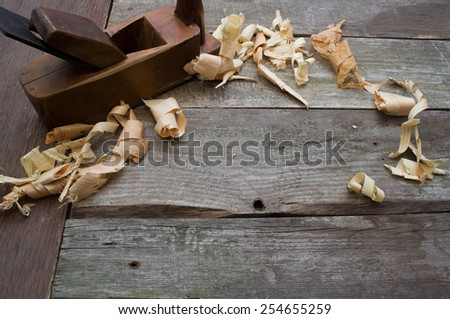 Old plane hand tool upper view. Old rusty and dirty carpenter`s wooden hand tools lying on a wooden table with sawdust background. - stock photo